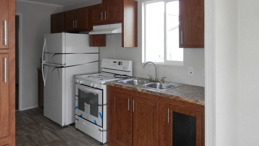 Freeman Kitchen Showing-  Vinyl Decor Wall Panels Throughout, Cabinets in Mountain Alder MDF Wrap, 18 Cubic Foot Frost Free Refridgerator, Laminate Counter Tops in Summer Carnival Throughout, Linoleum Flooring in Pamplona Color Throughout, Stainless Steel Deep Cell Sink, Dual Handle Faucet, 30 inch Vented Range Hood with Light. Upgrades Showing- 30 inch Gas Range 4 Burner Top.