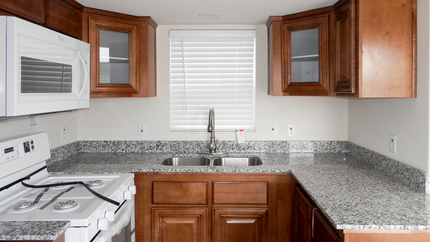 Sausalito Kitchen Showing- Tape and Textured Walls in Half Santas Beard Throughout, 2 Inch Faux Wood Blinds, Granite Counter Tops in Hamitlon Throughout, Deluxe Gas Range, Stainless Steel Sink. Options Showing- Space Saver Microwave, Cabinets in New Lance Throughout, Glass in Cabinet Doors.
